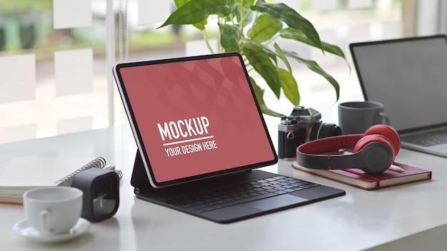 Przycięte ujęcie obszaru roboczego z makietą tabletu, laptopa, słuchawek, aparatu i materiałów eksploatacyjnych