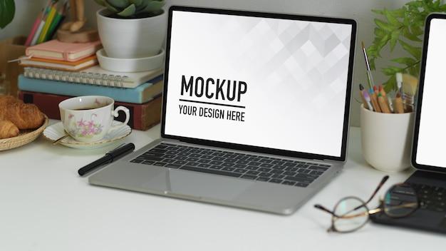 Przycięte ujęcie stołu roboczego z laptopem, tabletem, materiałami eksploatacyjnymi i dekoracjami