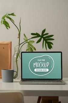 Przycięte ujęcie stołu roboczego z makietą laptopa, kubka, wazonu z roślinami i tablicy ogłoszeń w biurze domowym