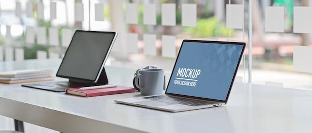 Przycięte ujęcie stołu roboczego z makietą laptopa, tabletu i materiałów eksploatacyjnych