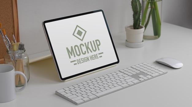 Przycięte ujęcie stołu roboczego z makietą tabletu i materiałów biurowych