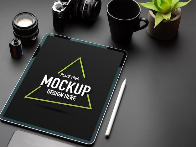 Przycięte zdjęcie czarnego stołu z makietą tabletu, aparatu, kubka, doniczki i miejsca na kopię