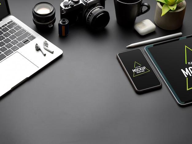 Przycięte zdjęcie czarnego stołu z makietą tabletu, smartfona, laptopa, aparatu i miejsca na kopię