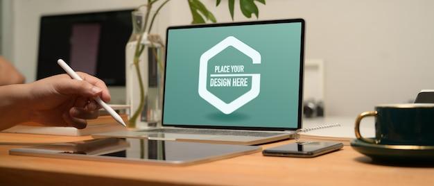 Przycięte zdjęcie dłoni za pomocą cyfrowego tabletu na drewnianym stole z makietą laptopa, smartfona
