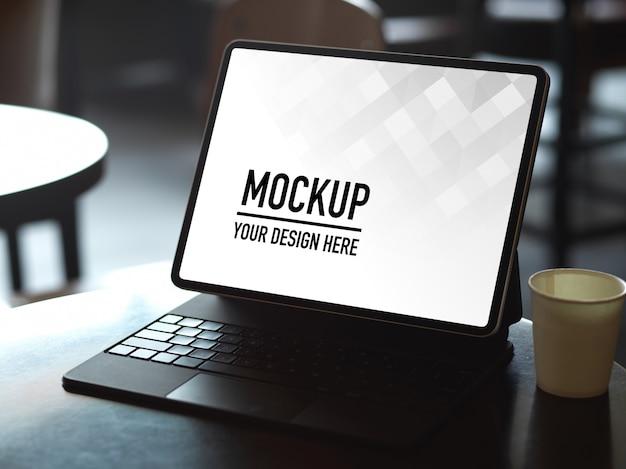 Przycięte zdjęcie makiety cyfrowego tabletu z klawiaturą i papierowym kubkiem na stoliku do kawy