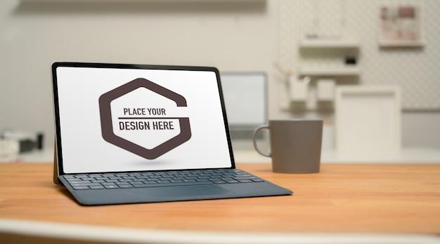 Przycięte zdjęcie makiety cyfrowego tabletu z klawiaturą, kubkiem do kawy i miejscem na kopię na drewnianym stole