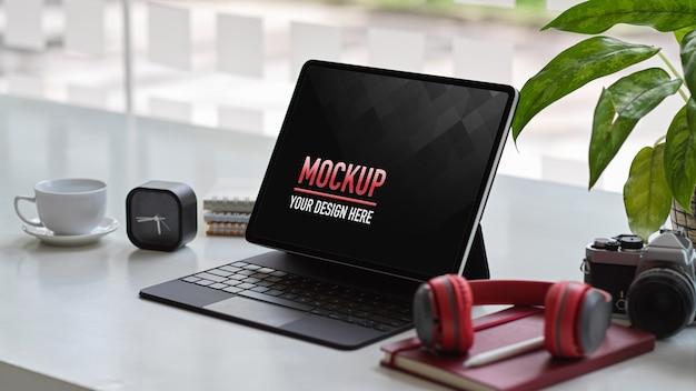 Przycięte zdjęcie makiety cyfrowego tabletu z klawiaturą, słuchawkami, aparatem i materiałami eksploatacyjnymi w biurze