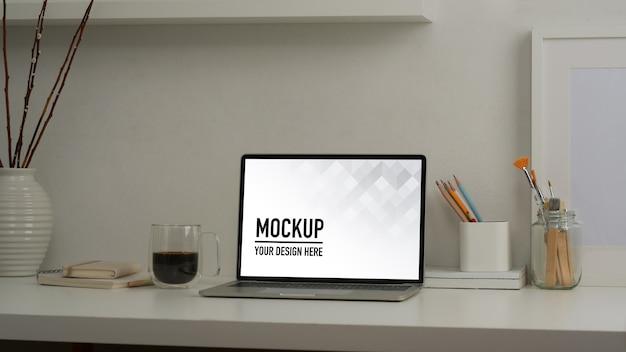 Przycięte zdjęcie makiety laptopa na białym stole z materiałami biurowymi