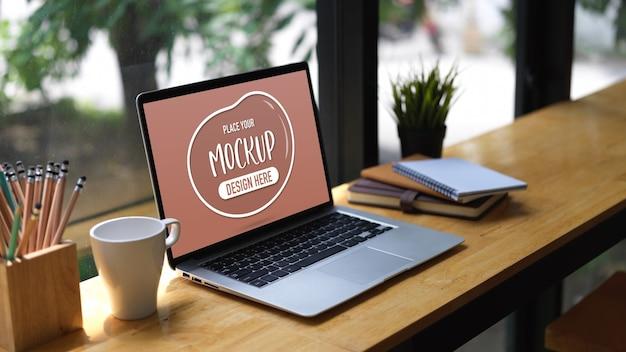 Przycięte zdjęcie makiety laptopa, papeterii, kubka i doniczki na drewnianym barze w kawiarni