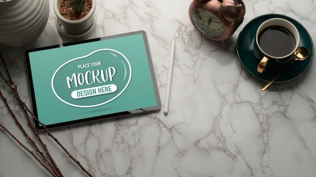 Przycięte zdjęcie marmurowego stołu z makietą tabletu, filiżanki kawy, dekoracji i miejsca na kopię
