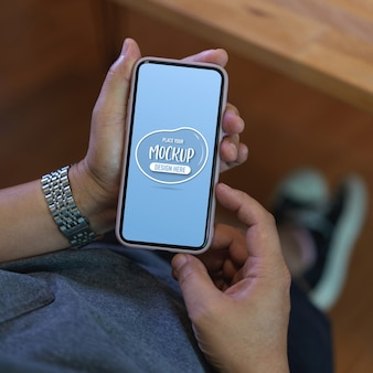 Przycięte zdjęcie męskich rąk trzymających makiety smartfona podczas zrelaksowanego siedzenia w miejscu pracy