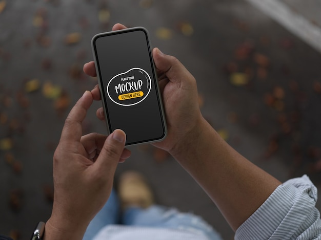Przycięte zdjęcie mężczyzny przy użyciu makiety smartfona podczas spaceru po ulicy