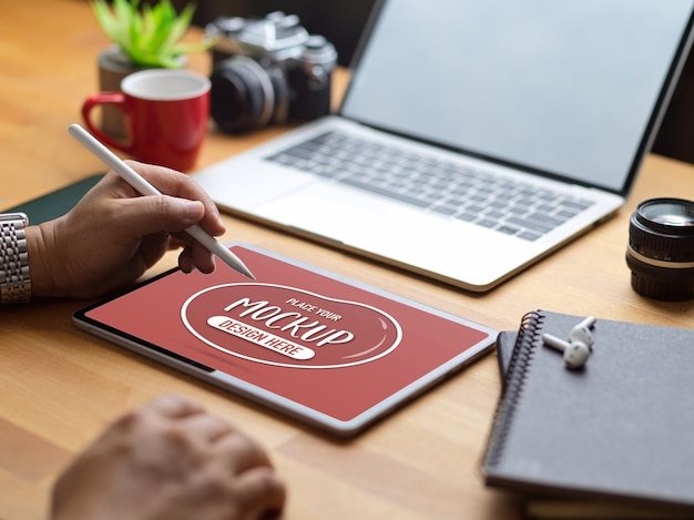 Przycięte zdjęcie mężczyzny rysującego na makiecie tabletu z rysikiem na drewnianym stole z materiałami biurowymi