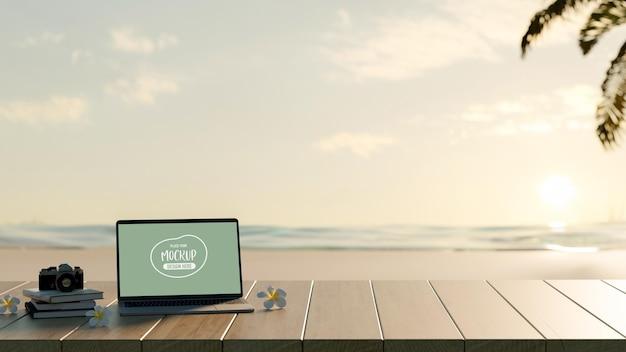 Przycięte zdjęcie pustego ekranu makiety laptopa z książką i aparatem na drewnianym stole z tłem morza