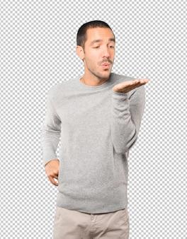 Przyjazny młody człowiek gestem wysyłania buziaka ręką