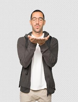 Przyjazny student wykonujący gest wysyłania buziaka ręką