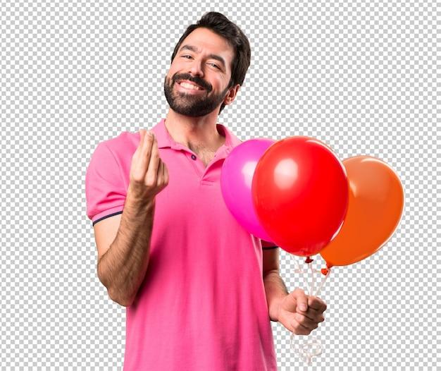 Przystojni młodego człowieka mienia balony i robić pieniądze gestykulują