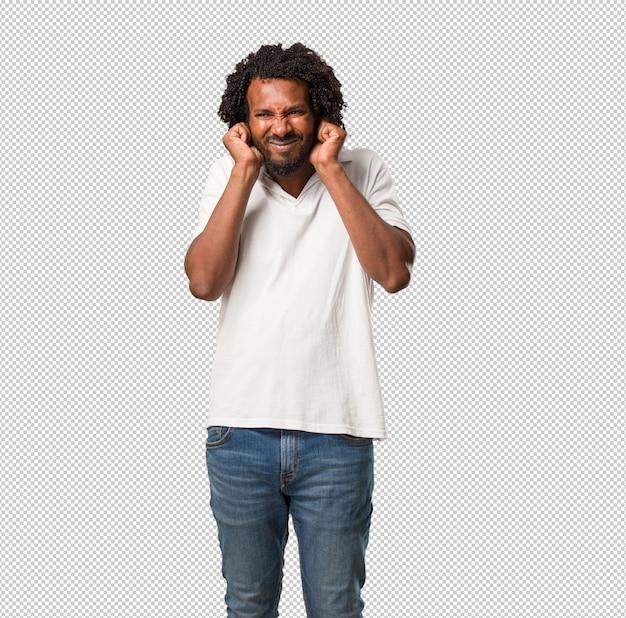 Przystojny afroamerykanin zakrywający uszy rękami, zły i zmęczony słyszeniem jakiegoś dźwięku