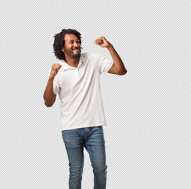 Przystojny amerykanin afrykańskiego pochodzenia słucha muzyka, tanczy zabawę, ma, rusza się, krzyczy i wyraża szczęście, wolności pojęcie