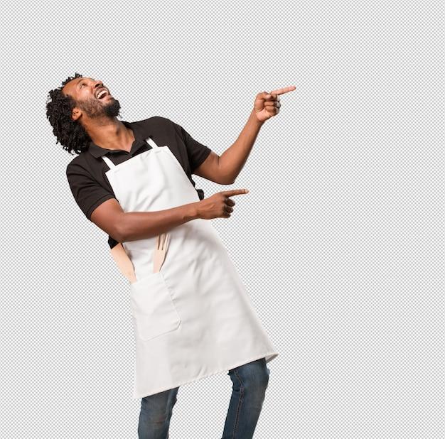 Przystojny amerykanina afrykańskiego pochodzenia piekarz wskazuje na bok, uśmiecha się zaskoczony, prezentując coś naturalnego i swobodnego