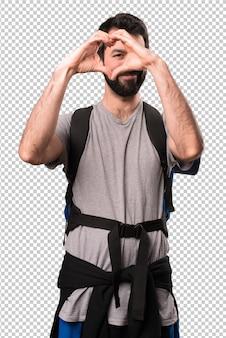 Przystojny backpacker robi sercu z jego rękami