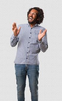 Przystojny biznesmen afroamerykanów, śmiejąc się i dobrze się bawiąc, będąc zrelaksowany i wesoły, czuje się pewnie i sukces