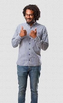 Przystojny biznesowy amerykanina afrykańskiego pochodzenia mężczyzna rozochocony i podekscytowany, uśmiecha się jej kciuk up i podnosi, pojęcie sukces i zatwierdzenie, ok gest