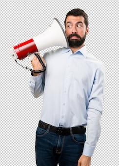 Przystojny mężczyzna trzyma megafon z brodą
