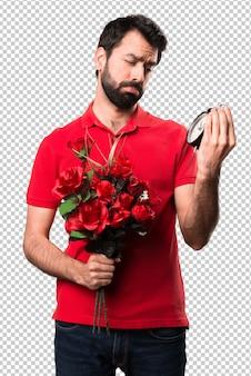 Przystojny mężczyzna mienie kwitnie trzymający rocznika zegar