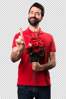 Przystojny mężczyzna trzyma kwiaty liczenia jeden