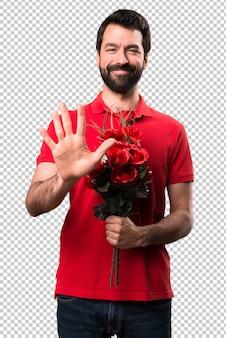 Przystojny mężczyzna trzyma kwiaty liczenia pięć