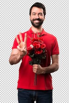 Przystojny mężczyzna trzyma kwiaty liczenia trzy
