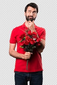 Przystojny mężczyzna trzyma kwiaty myślenia