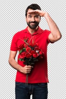 Przystojny mężczyzna trzyma kwiaty pokazano coś