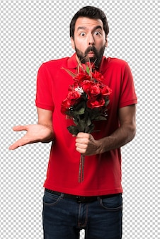 Przystojny mężczyzna trzyma kwiaty robi nieistotnemu gestowi