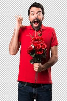 Przystojny mężczyzna trzyma kwiaty robi niespodzianka gestowi