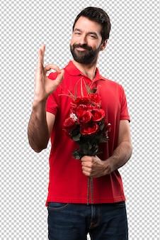 Przystojny mężczyzna trzyma kwiaty robi ok znakowi