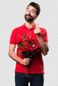 Przystojny mężczyzna trzyma kwiaty robi pieniądze gestowi