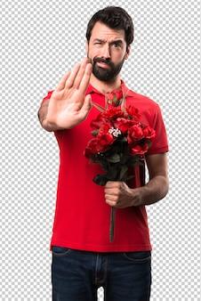 Przystojny mężczyzna trzyma kwiaty robi przerwie podpisywać