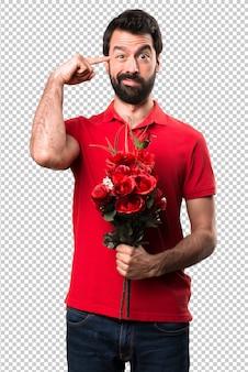 Przystojny mężczyzna trzyma kwiaty robi szalonemu gestowi