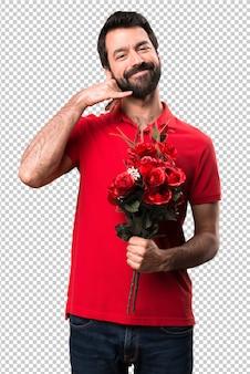 Przystojny mężczyzna trzyma kwiaty robi telefonowi gestykulować