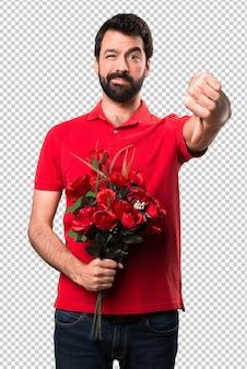 Przystojny mężczyzna trzyma kwiaty robi złemu sygnałowi