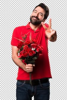 Przystojny mężczyzna trzyma kwiaty robi zwycięstwo gestowi