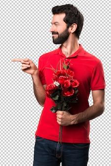 Przystojny mężczyzna trzyma kwiaty wskazuje lateral