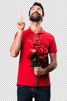 Przystojny mężczyzna trzyma kwiaty wskazuje up