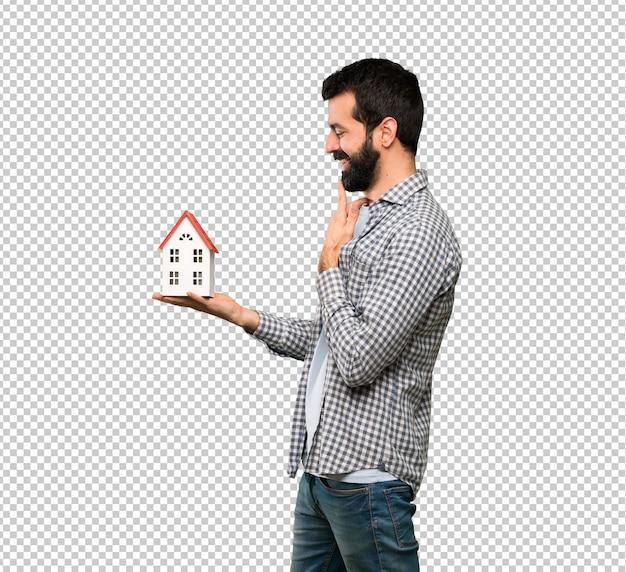 Przystojny mężczyzna trzyma troszkę dom z brodą