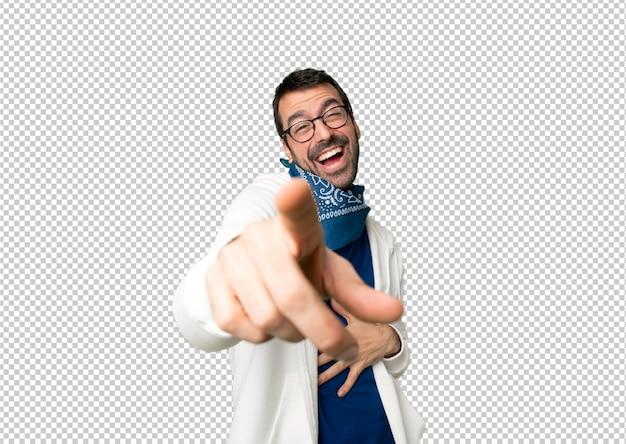 Przystojny mężczyzna wskazuje z palcem przy someone i śmia się dużo z szkłami