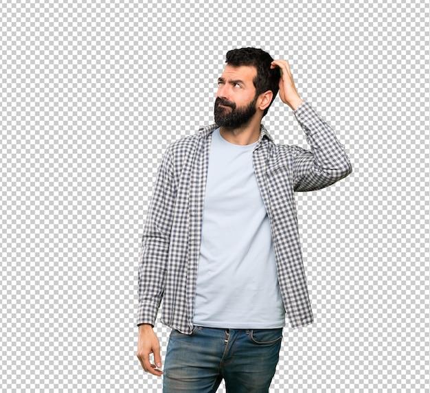 Przystojny mężczyzna z brodą ma wątpliwości podczas drapania głowy