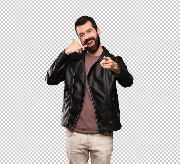 Przystojny mężczyzna z brodą robi gestowi telefonu i wskazuje przód