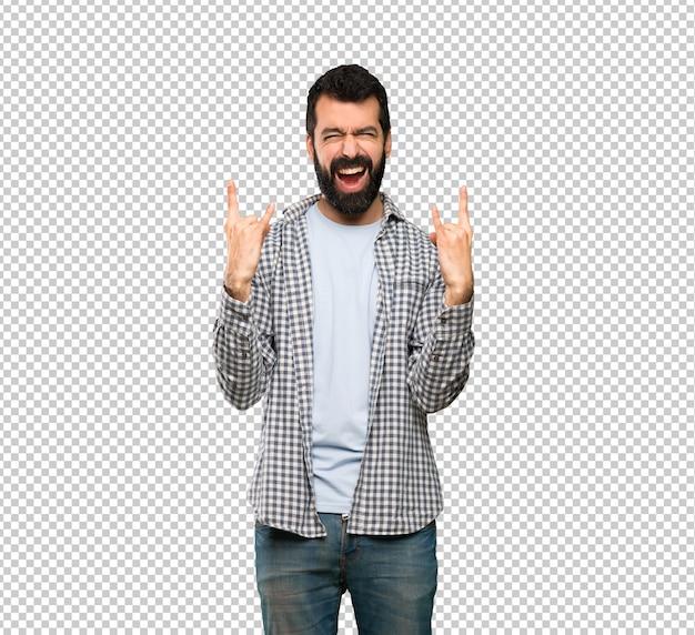 Przystojny mężczyzna z brodą robi rockowemu gestowi